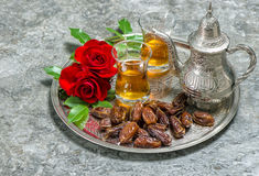 Tea, dates fruits and flowers. Islamic holidays decoration. Eid. Tea, dates fruits and red rose flowers. Islamic holidays decoration. Eid al-Fitr. Oriental Royalty Free Stock Image