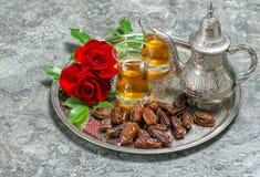 Tea, dates fruits and flowers. Islamic holidays decoration. Eid Royalty Free Stock Image