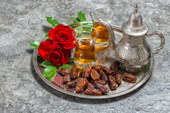 Tea, dates fruits and red rose flowers. Islamic holidays decorat Stock Image