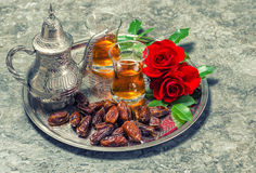 Tea, dates fruits and red rose flowers. Oriental hospitality con Royalty Free Stock Photography