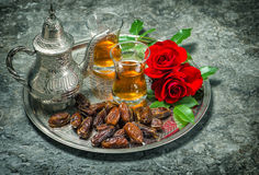 Tea, dates fruits and red rose flowers. Oriental hospitality vin Stock Photos