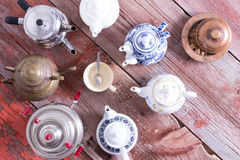 Tea on demand concept. With a radiating circle of teapots arranged with their spouts facing a central empty cup and teaspoon on a rustic wooden table, overhead stock photos