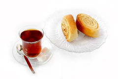 Tea and dessert rolls. A cup of well steeped Turkish tea served with dessert rolls Stock Image
