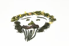 Tea of different varieties is laid out on a white background in the form of a picture - a person`s face! The image used black, gre. Tea, a lot of tea, kinds of stock photo