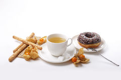 Tea , donut, sesame cookies and physalis Stock Images