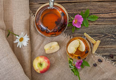 Tea with dried dog-rose and apples on a wooden table Stock Images