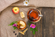 Tea with dried dog-rose and apples on a wooden table Stock Photos