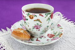 Tea drinking. Cup with the black tea and the cookies Stock Images