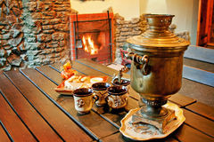 Tea drinking with samovar at a fireplace Stock Photo