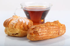 Tea with eclair and profiterole Royalty Free Stock Images