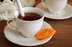 Tea in elegant porcelain cups, candied oranges Royalty Free Stock Images
