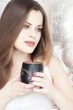 Tea eller kaffe för härlig flicka dricka Skönhetkvinna med koppen av den varma drycken Tycka om kaffe Varma pastellfärgade färger Fotografering för Bildbyråer