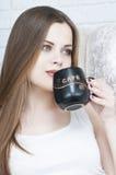 Tea eller kaffe för härlig flicka dricka Skönhetkvinna med koppen av den varma drycken Tycka om kaffe Varma pastellfärgade färger Arkivbild