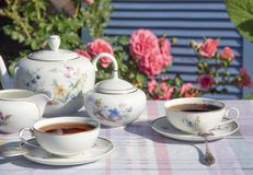 Tea in the English style on the background of roses stock images