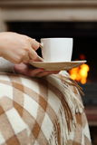 Tea by the fireplace. Woman having tea by the fireplace Royalty Free Stock Image