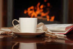 Tea by the fireplace. Tea, book and shawl by the fireplace Royalty Free Stock Photography