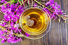Tea from fireweed in glass cup on board top Stock Photo