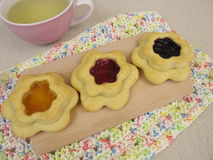 Tea and floret biscuits filled with jam. On crocheted doily Royalty Free Stock Images