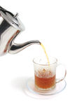 Tea flow from kettle to cup Stock Photos