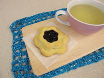 Tea and flower biscuit filled with jam Royalty Free Stock Photography
