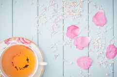 Tea and flowers. Black tea in china teacup, lilac flowers and scattered petals of rose royalty free stock photo
