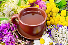 Tea from flowers in clay cup on board Royalty Free Stock Photography