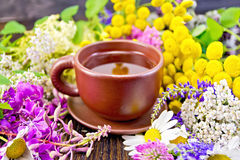 Tea from flowers in clay cup on dark board Stock Photo
