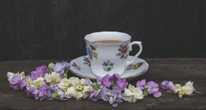 Tea and flowers. Delicate pastel coloured flowers and bone china stock images