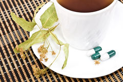 Tea from the flowers of linden and tablets. Stock Photo