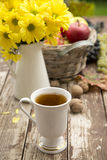 Tea in a flu season. Cup of tea in a cold season ,with fruits and flowers of autumn in background Stock Photos