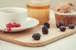 Tea with fresh berries, cake and honey/healthy breakfast: tea with fresh berries, cake and honey on a wooden surface. Cup brunch food background table snack stock photo