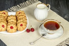 Tea fresh biscuits with cherries. On the table in the morning on nature Stock Image