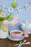 Tea and fresh tulips. Tea in colorful vintage cup and fresh pink tulips stock image