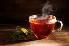 Tea freshly brewed in a glass cup and some herbs on a dark rusti. C wooden background, healthy hot drink against cold and flu, copy space, selected focus Stock Images