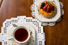 Tea and fruit cake. Top view of tea cup and fruit cake on table Royalty Free Stock Image