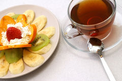 Tea and fruit salad. Crystal tea cup and fruit salad Royalty Free Stock Photography