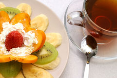 Tea and fruits. Hot black tea and fruit salad Stock Image