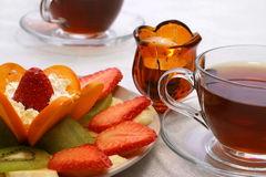 Tea and fruits. Black tea with fruits salad and candle Royalty Free Stock Image