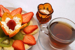 Tea fruits and candle. Hot black tea with fruit salad and alight candle Stock Photography
