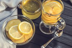 Tea with ginger and lemon in a glass cup and yellow sweets Royalty Free Stock Images