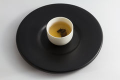 Tea glass on black dish. Royalty Free Stock Photos