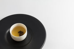 Tea glass on black dish. Stock Images