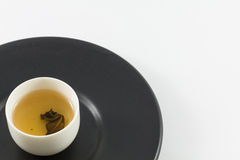 Tea glass on black dish. Royalty Free Stock Photography