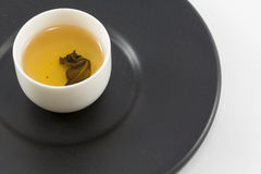 Tea glass on black dish. Stock Photos