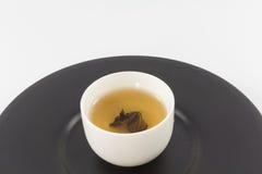 Tea glass on black dish. Stock Image