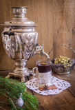 Tea in glass with coaster and russian samovar on wooden background. Home christmas decoration Stock Photography