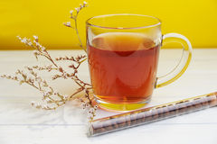 Tea in glass cup with coffee beans on yellow background Royalty Free Stock Photos