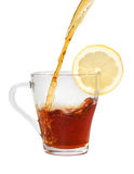 Tea in the glass cup with lemon. Stream of ice tea pouring the glass cup with a slice of lemon on it Stock Photo