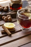 Tea in glass cup with lemon and vanilla pod at wood background. Hazelnut and jam in jar at wood board behind. stock image