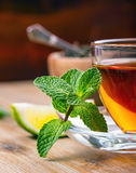 Tea in a glass cup, mint leaves, dried tea, sliced lime, cane sugar Stock Photo